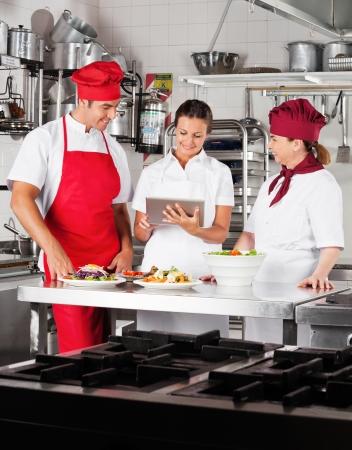 Chefs Using Digital Tablet In Kitchen photo