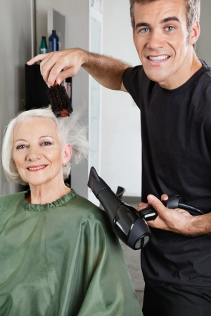 Hair Stylist Blow Drying Senior Woman s Hair photo