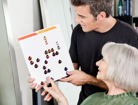 Woman With Male Hair Stylist Selecting Hair Color photo