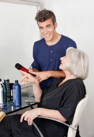 Hairdresser Showing Hair Product To Client photo