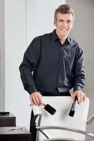 Happy Hairdresser Holding Straightener And Brush Stock Photo - 18394001