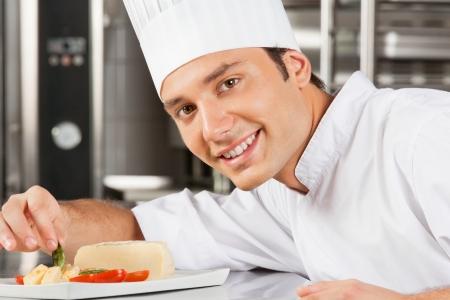 garnishing: Happy Male Chef Garnishing Dish