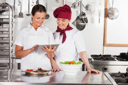 commercial kitchen: Female Chefs Using Digital Tablet