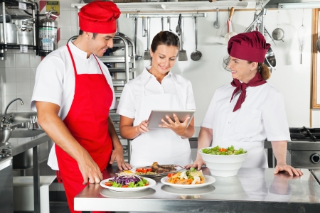 Chefs Using Tablet Computer In Kitchen photo