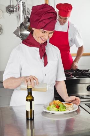 aceite de cocina: Aceite Cocinero de sexo femenino Verter en el plato
