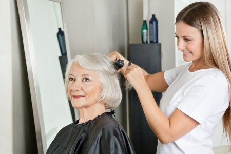 Hairstylist Straightening Woman s Hair At Salon photo