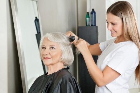 parlor: Hairstylist Straightening Woman s Hair At Salon Stock Photo