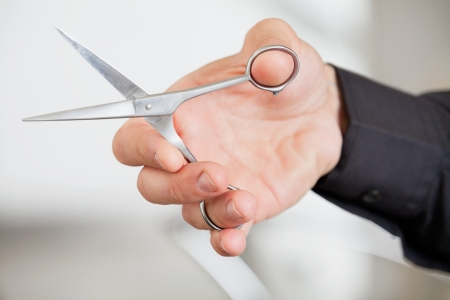 Male Hairdresser s Hand Holding Scissors photo