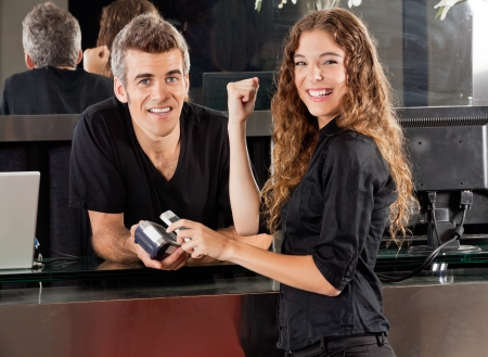 nfc: Happy Woman Paying Through Cellphone At Salon Counter