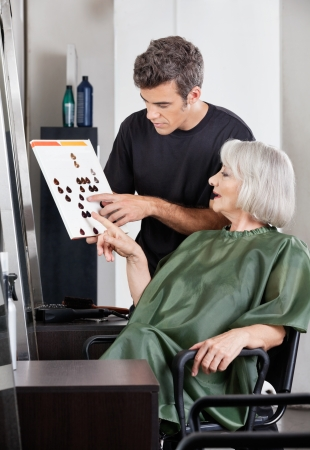Hairdresser Advising Female Client In Selecting Color photo