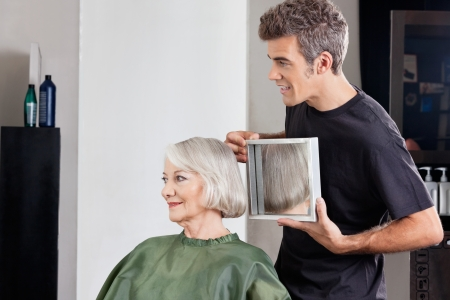 Hairstylist Showing Finished Haircut To Customer At Parlor photo
