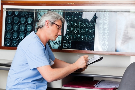 Doctor Writing On Clipboard Stock Photo - 18521587
