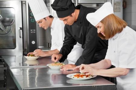 garnishing: Chefs Garnishing Dishes On Counter Stock Photo