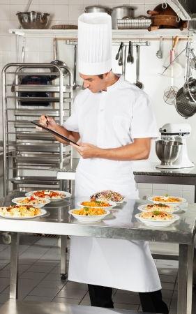 food inspection: Chef With Clipboard Checking Pasta Dishes Stock Photo