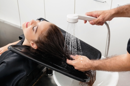 woman washing hair: Hairstylist Washing Client s Hair At Parlor
