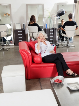 beauty parlor: Client Holding Magazine While On Call At Salon