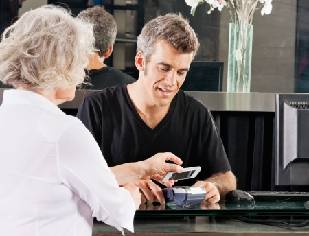 wireless terminals: Customer Paying Through Mobile Phone At Salon Stock Photo