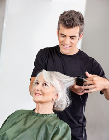 beauty parlor: Hairstylist Straightening Senior Woman s Hair