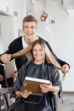 Hairstylist With Client Holding Mirror At Salon photo