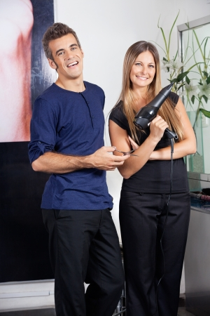 Happy Hairdressers Holding Scissors And Hairdryer photo