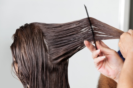 combing hair: Hands Of Hairdresser Combing Client s Hair Stock Photo
