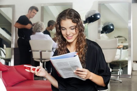 Woman With Mobile Phone Reading Magazine At Hair Salon photo