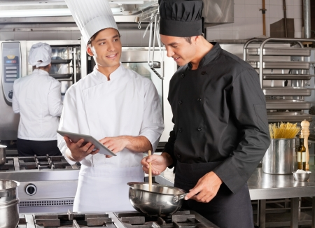 Male Chef Assisting Colleague In Preparing Food Stock Photo - 18793402