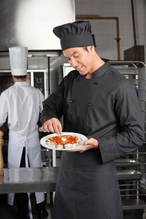 Chef Garnishing Dish In Kitchen Stock Photo - 18793406