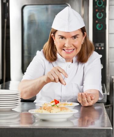 garnishing: Mature Female Chef Garnishing Dish Stock Photo