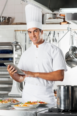 Young Chef Holding Tablet With Pasta Dishes At Counter photo