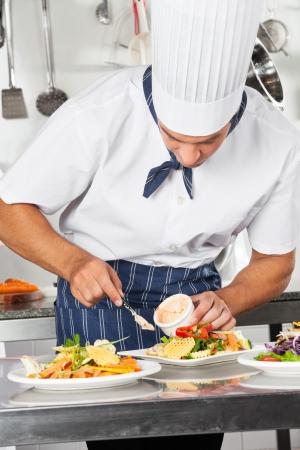 garnishing: Chef Garnishing Dish With Mayonnaise Stock Photo