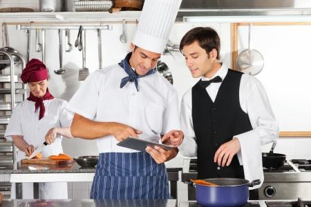 cocinas industriales: Camarero y cocinero que usa la tableta digital en la cocina Foto de archivo