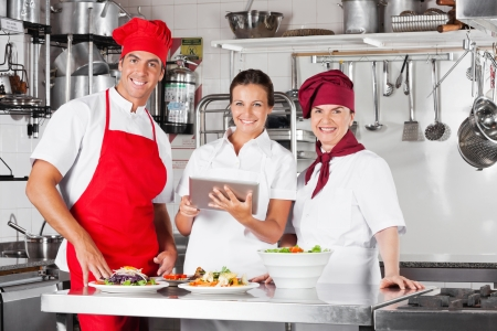 Happy Chefs Using Tablet Computer In Kitchen Stock Photo - 18793648