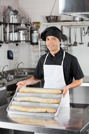 Male Chef Presenting Loafs In Kitchen Stock Photo - 18793409