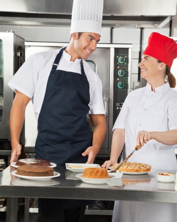 Happy Chefs Preparing Sweet Dishes in Kitchen Stock Photo - 18793640