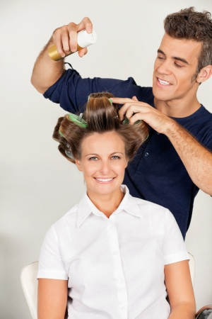 hairspray: Customer With Hairstylist Setting Curls With Hairspray