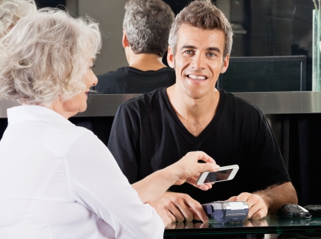 Hairdresser With Woman Paying Through Cellphone Stock Photo - 18793396