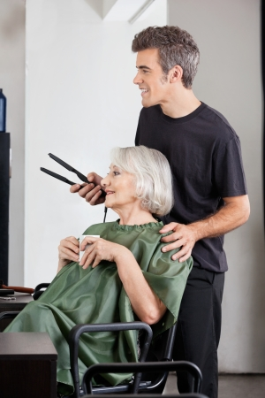 Woman With Coffee Cup And Hairdresser Holding Straightener photo