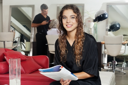Client Holding Magazine With Hairdresser Working At Salon photo
