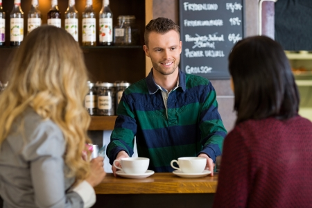 serving: Bartender Serving Coffee To Female Friends At Cafe