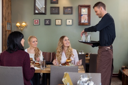 out of order: Waiter With Tray Of Glasses While Female Customers Having Meal