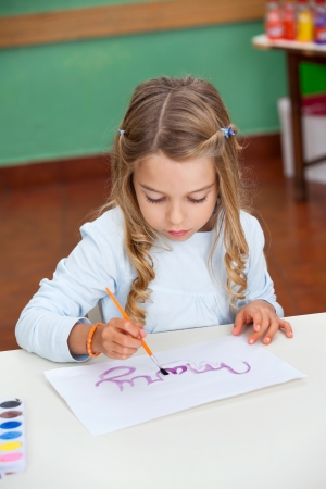 Girl Painting Name On Paper At Desk photo