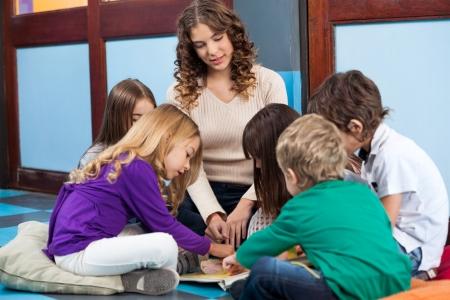 preescolar: Profesor y estudiantes libro de lectura en preescolar