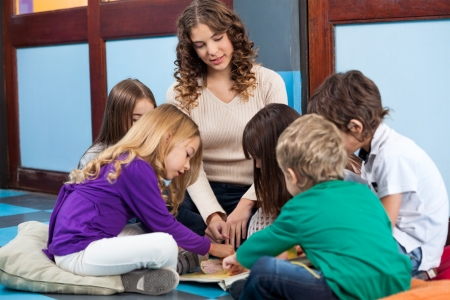 daycare: Teacher And Students Reading Book In Preschool