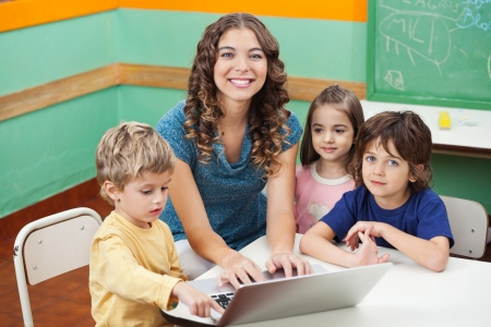 Beautiful Teacher And Students With Laptop In Classroom photo