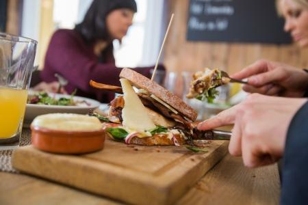 adult sandwich: Businessman Having Burger With Colleagues