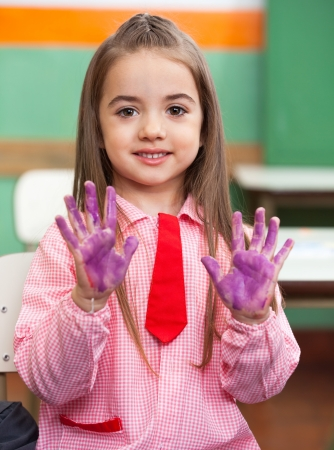Girl Showing Colored Hands In Classroom Stock Photo - 20592476