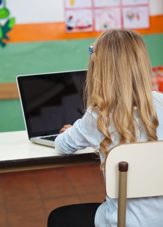 Little Girl Using Laptop In Preschool photo