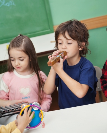 flute instrument: Children Playing Musical Instruments In Classroom Stock Photo