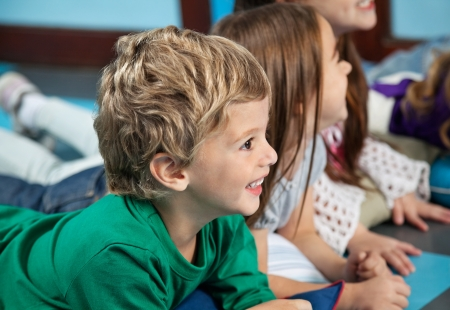 day care: Boy With Friends Lying On Floor In Kindergarten